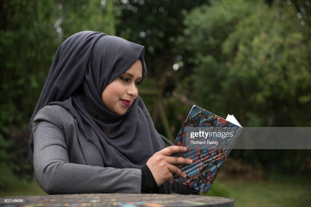 Portrait of a young lady wearing a hijab reading abook in the garden : Stock Photo