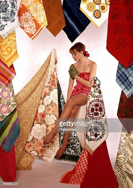 1967 A portrait of a young lady with dark hair wearing a towel whilst sitting rubbing a fannel over herself amongst a number of multicoloured fabrics...