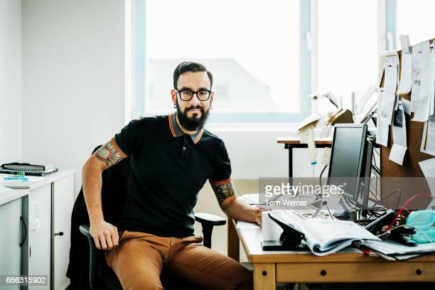 Portrait of a young latin businessman sitting on a desk