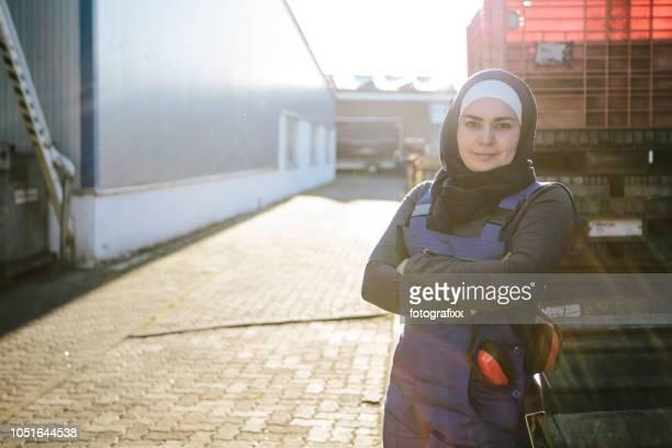 portret van een jonge lachen vrouwelijke technicus in werkplaats, camera kijken - wedding veil stockfoto's en -beelden