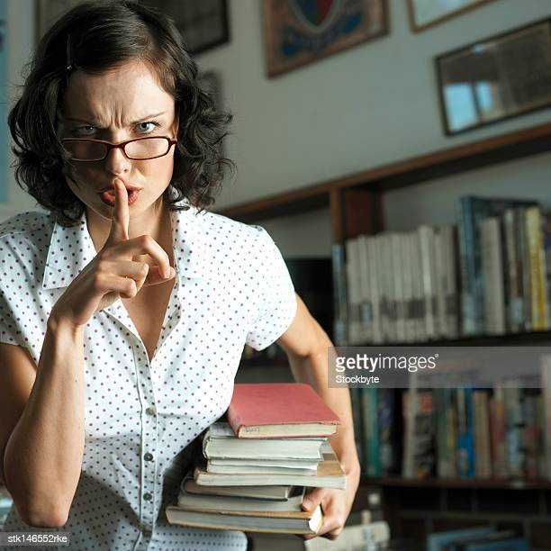portrait of a young librarian indicating silence