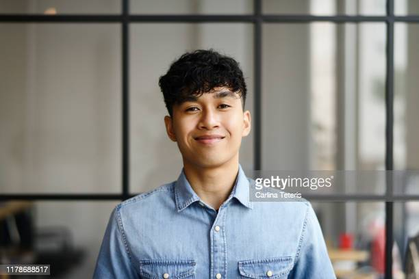 portrait of a young malay man in a modern office - asien stock-fotos und bilder