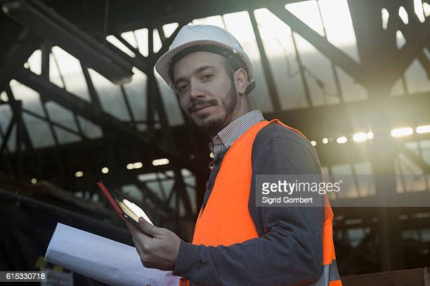portrait of a young male engineer holding blueprint and using digital tablet at construction site, freiburg im breisgau, baden-württemberg, germany - sigrid gombert photos et images de collection