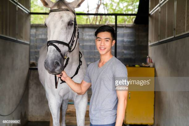 Portrait of a young male horse rider stood with his horse