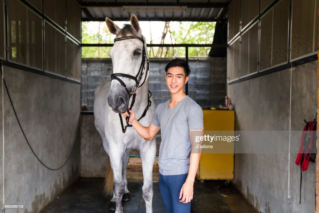 Portrait of a young male horse rider stood with his horse : Stock Photo