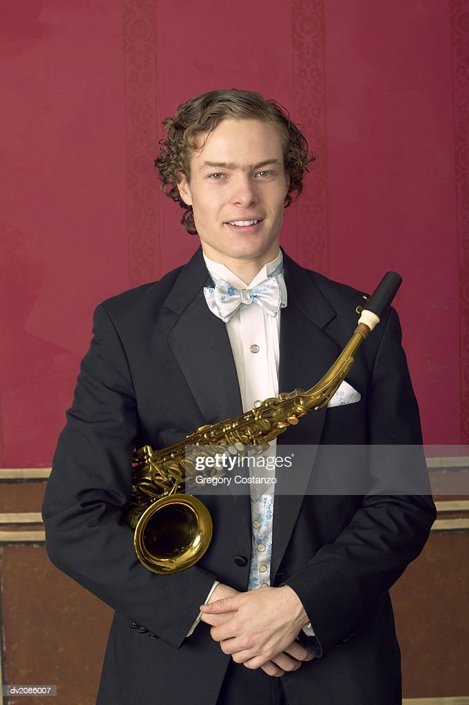 Portrait of a Young Male Saxophonist in an Old-Fashioned Suit : Stock Photo
