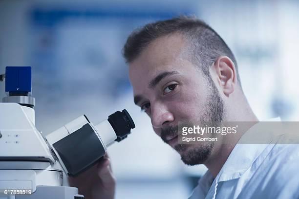 """portrait of a young male scientist using microscope in an optical laboratory, freiburg im breisgau, baden-württemberg, germany"" - sigrid gombert stock-fotos und bilder"