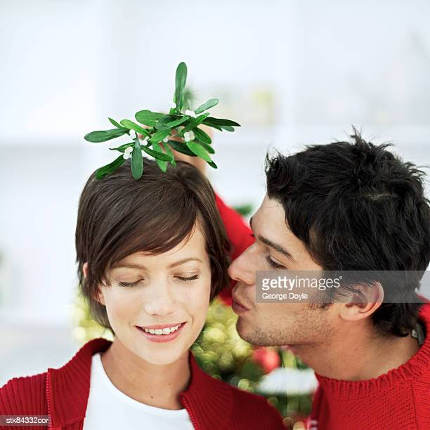 portrait of a young man about to kiss a young woman on the cheek while holding a plant above her head - heterosexuelles paar stock-fotos und bilder