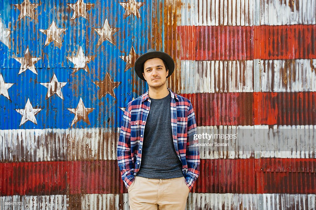 Portrait of a young man against American flag : Stock Photo