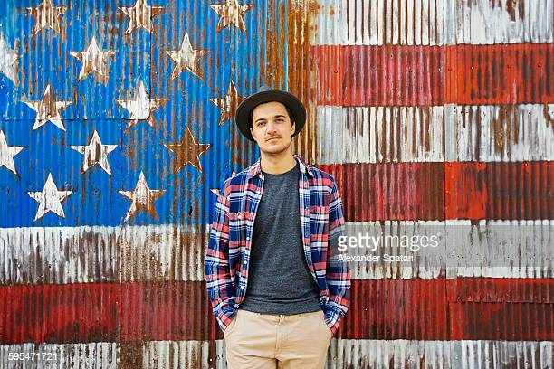 Portrait of a young man against American flag