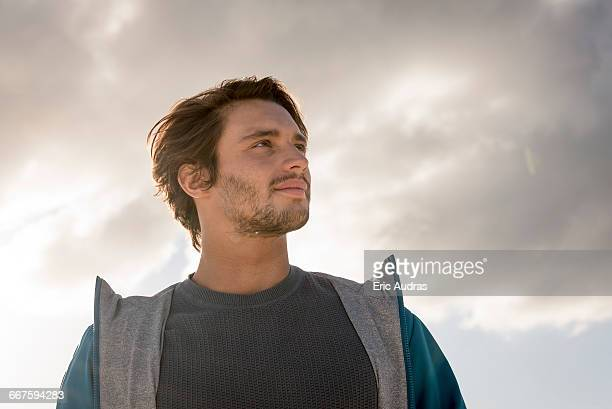 portrait of a young man against cloudy sky - low angle view stock pictures, royalty-free photos & images