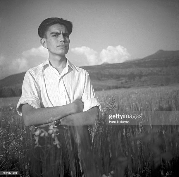 Portrait of a young man as he stands, arms crossed, in a field of wheat, La Reina, Santiago Region, Chile, April 23, 1940.