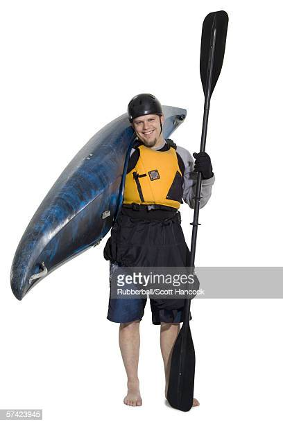 Portrait of a young man carrying a kayak and an oar
