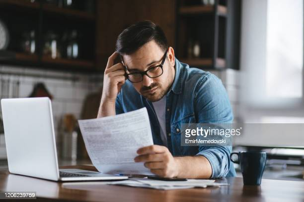 portrait of a young man checking home finances - bank account stock pictures, royalty-free photos & images