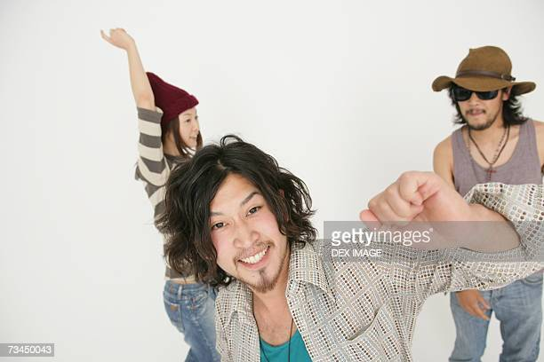 Portrait of a young man dancing with his friends and looking cheerful