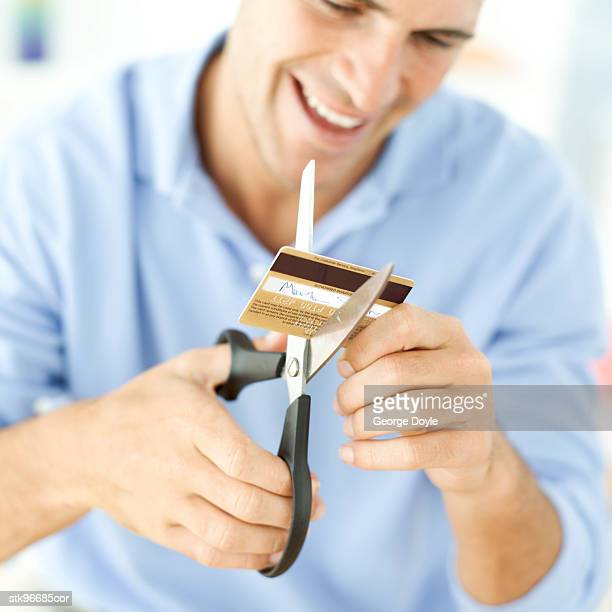 portrait of a young man destroying his credit card with a pair of scissors