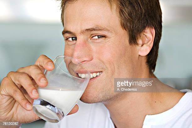 Portrait of a young man drinking glass of milk