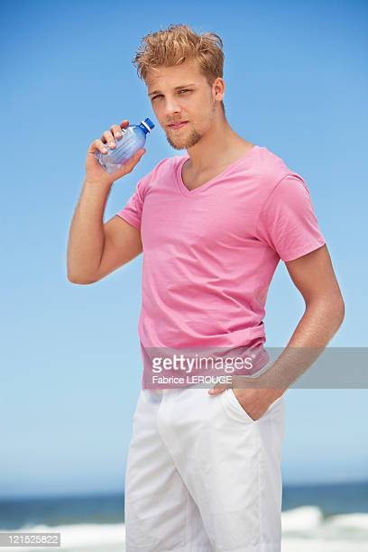 Portrait of a young man drinking water from a water bottle on the beach