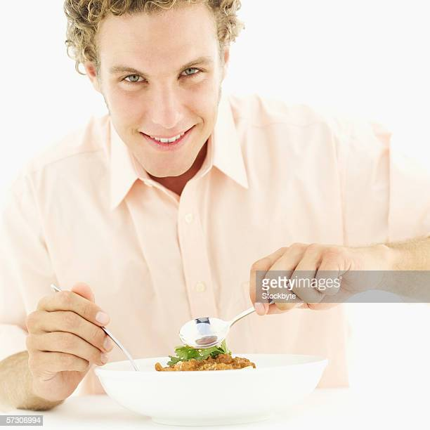 Portrait of a young man eating a bowl of rice and curry