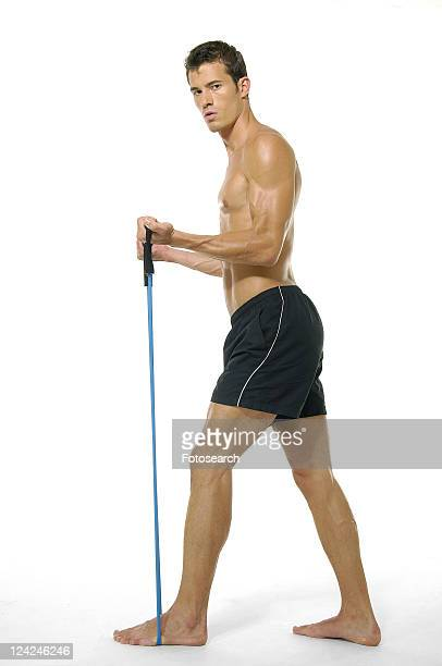Portrait of a young man exercising with a resistance band
