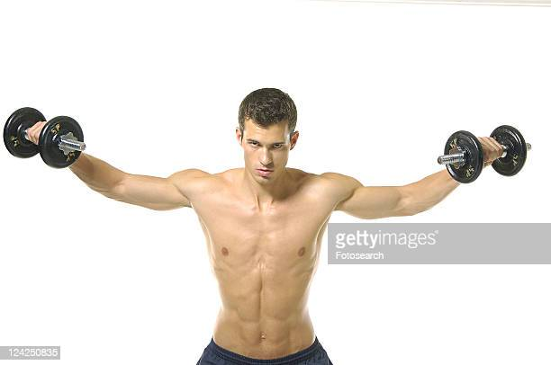 Portrait of a young man exercising with hand weights