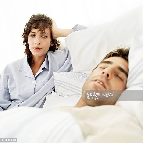 portrait of a young man fast asleep while his wife glares at him