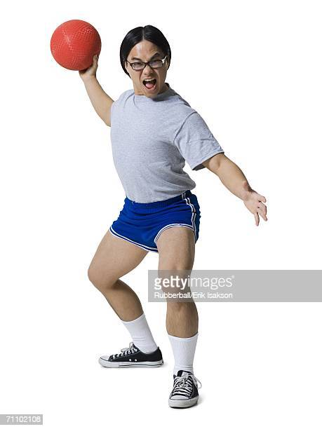 Portrait of a young man getting hit with a dodgeball