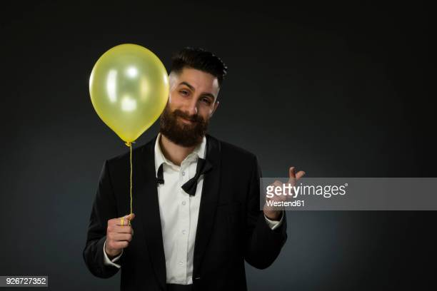 Portrait of a young man holding a balloon, wearing loose black tie