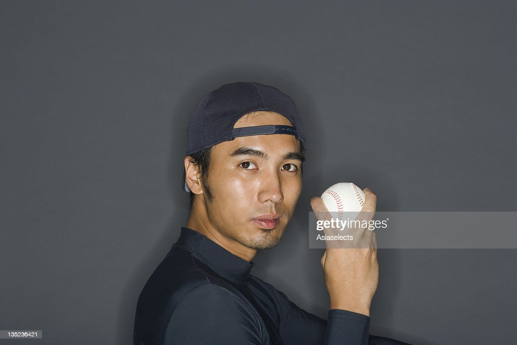 Portrait of a young man holding a baseball : Stock Photo