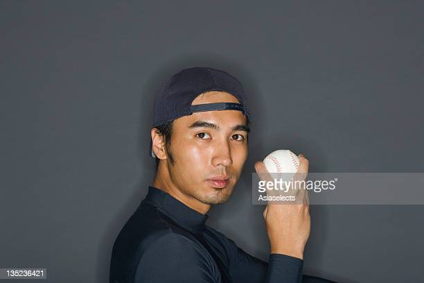 portrait of a young man holding a baseball - baseball trajectory stock photos and pictures