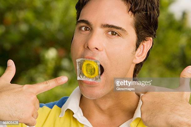 Portrait of a young man holding a condom in his mouth