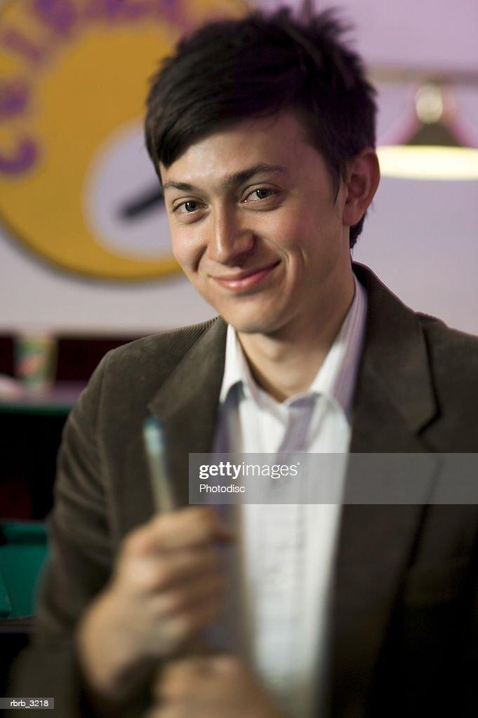Portrait of a young man holding a cue stick smiling : Foto de stock
