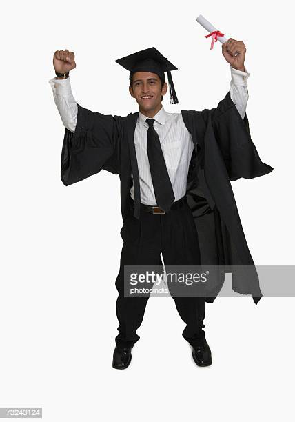Portrait of a young man holding a diploma and smiling