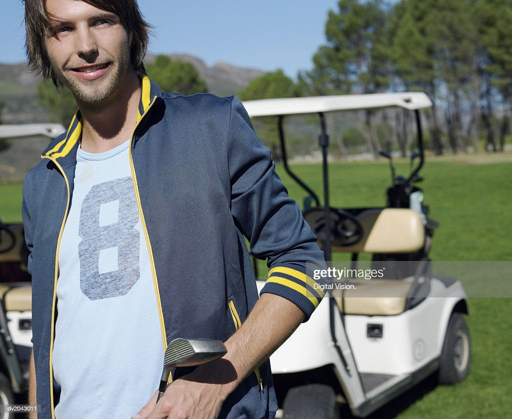 Portrait of a Young Man Holding a Golf Club with a Golf Buggy in the Background : Stock Photo