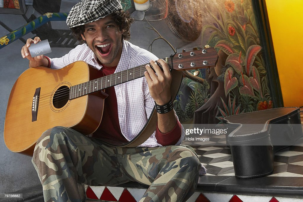 Portrait of a young man holding a guitar and a credit card : Stock Photo
