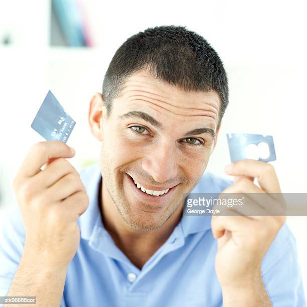 portrait of a young man holding a half of a destroyed credit card in each hand