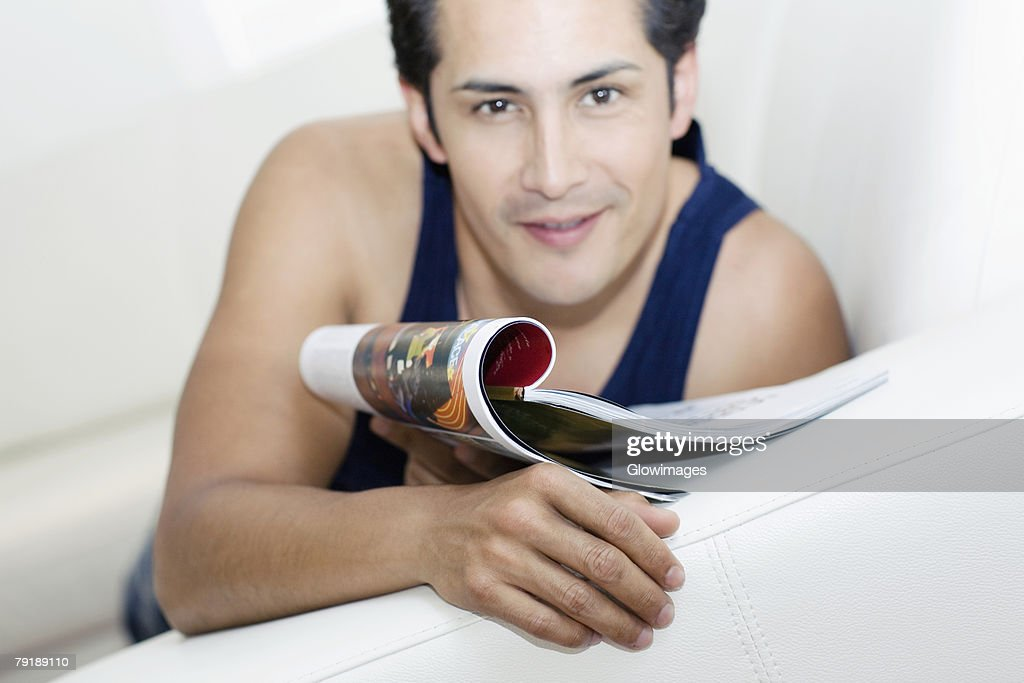 Portrait of a young man holding a magazine and smiling : Foto de stock