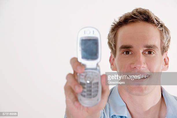 Portrait of a young man holding a mobile phone