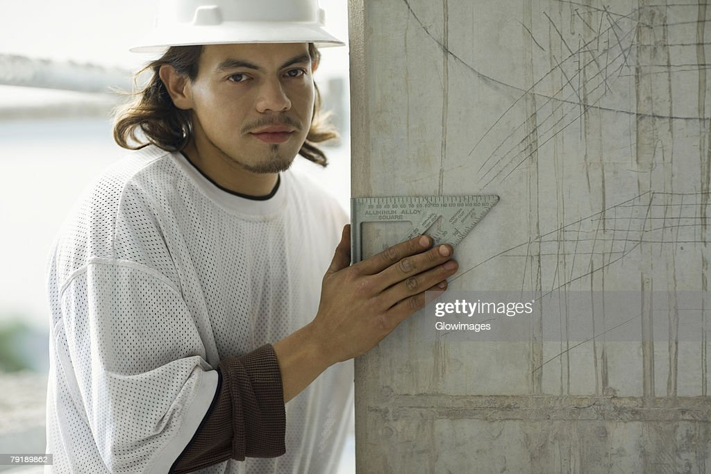 Portrait of a young man holding a set square : Stock Photo