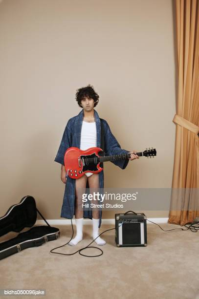 portrait of a young man holding an electric guitar - nachthemd stockfoto's en -beelden