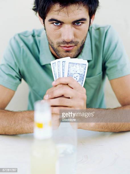 Portrait of a young man holding playing cards