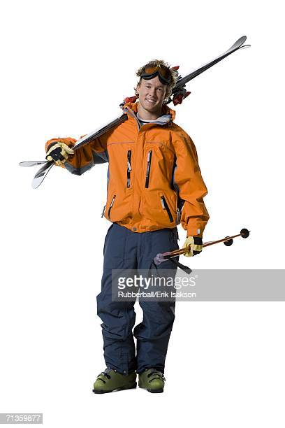 Portrait of a young man holding skis and ski poles