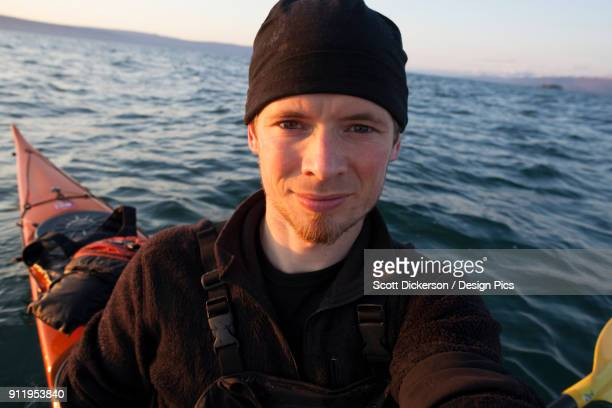 portrait of a young man in a kayak on the water at sunset, kachemak bay state park - kachemak bay stock pictures, royalty-free photos & images