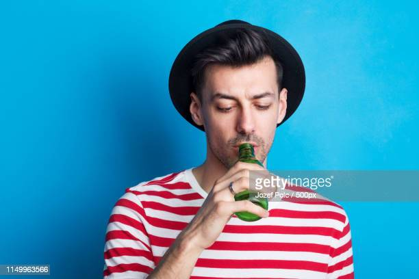 portrait of a young man in a studio drinking from a bottle on a blue background - ボーダーシャツ ストックフォトと画像