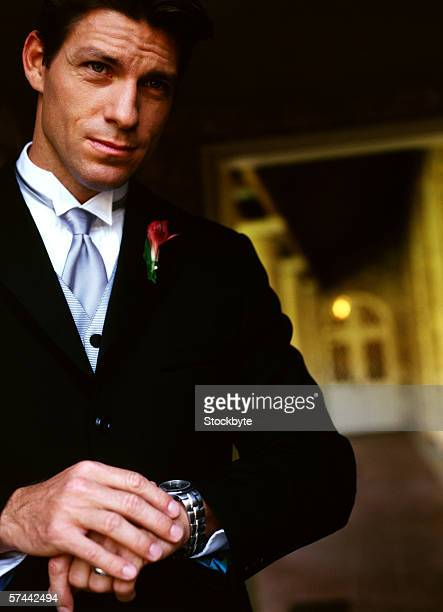 portrait of a young man in a tuxedo looking at his watch - impatience flowers stock pictures, royalty-free photos & images