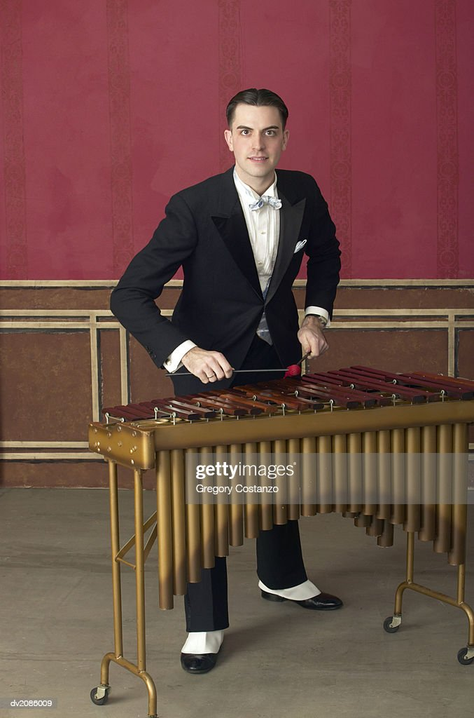 Portrait of a Young Man in an Old-Fashioned Suit Playing the Xylophone : Stock Photo