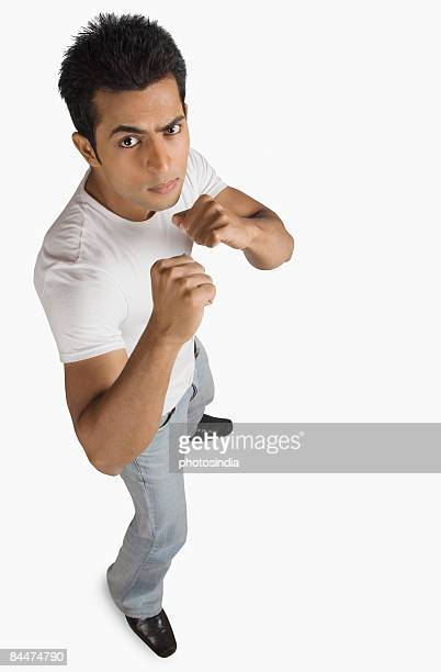 portrait of a young man in fighting stance - fighting stance stock pictures, royalty-free photos & images