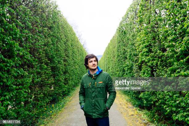 portrait of a young man in green maze tunnel - escapism stock pictures, royalty-free photos & images