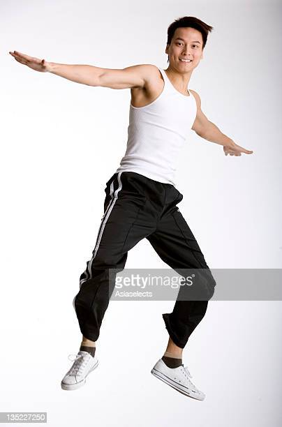 portrait of a young man jumping with his arms outstretched - vest stock pictures, royalty-free photos & images
