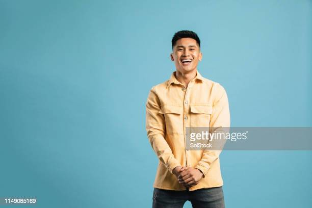 portrait of a young man laughing - coloured background stock pictures, royalty-free photos & images